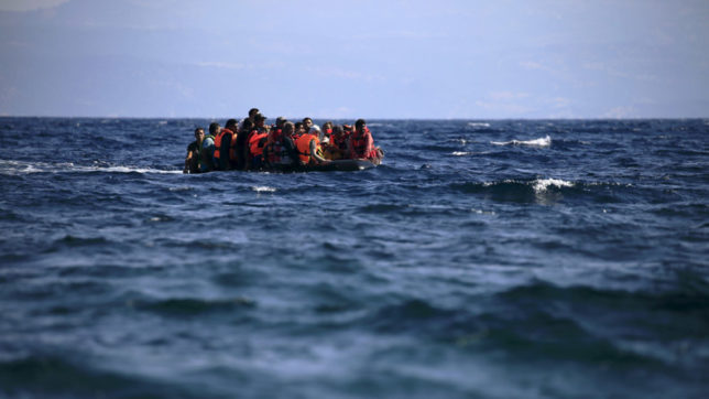 Syrian refugees on a dinghy approach, in rough seas, a beach on the island of Lesbos