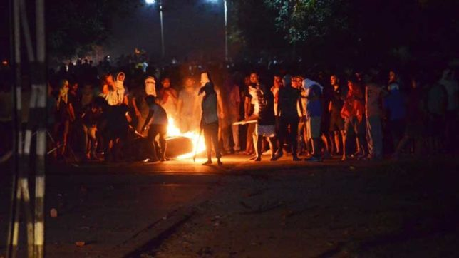 Varanasi: Students of the Banaras Hindu University (BHU) induldge in arson while protesting against the molestation of a student in the campus in Varanasi on Sept 23, 2017. (Photo: IANS)