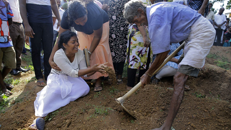 Wasanthi, a member of Berlington family weeps over the gave of Bevon, who was killed in the Easter Sunday bombings in Colombo, Sri Lanka on Tuesday, April 23, 2019. (AP Photo/Eranga Jayawardena)